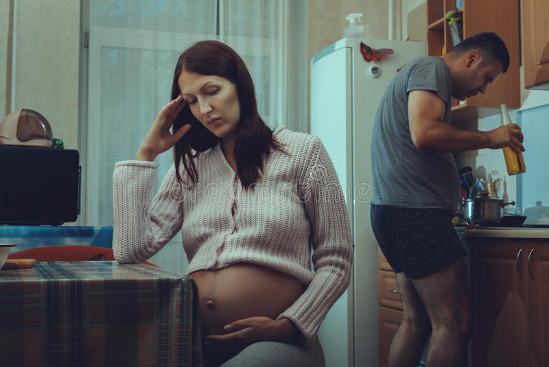 Zwangere vrouwenzitting en droevig, haar alcohol van echtgenootdranken royalty-vrije stock afbeelding