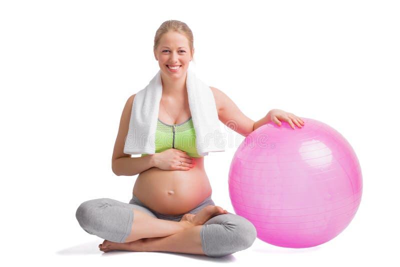 Zwangere vrouwenzitting in lotusbloempositie met geneeskundebal stock foto's