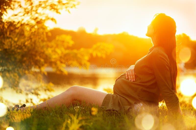 Zwangere vrouwenzitting op groen gras in de zomerpark, die van aard genieten Gezonde Zwangerschap stock foto's