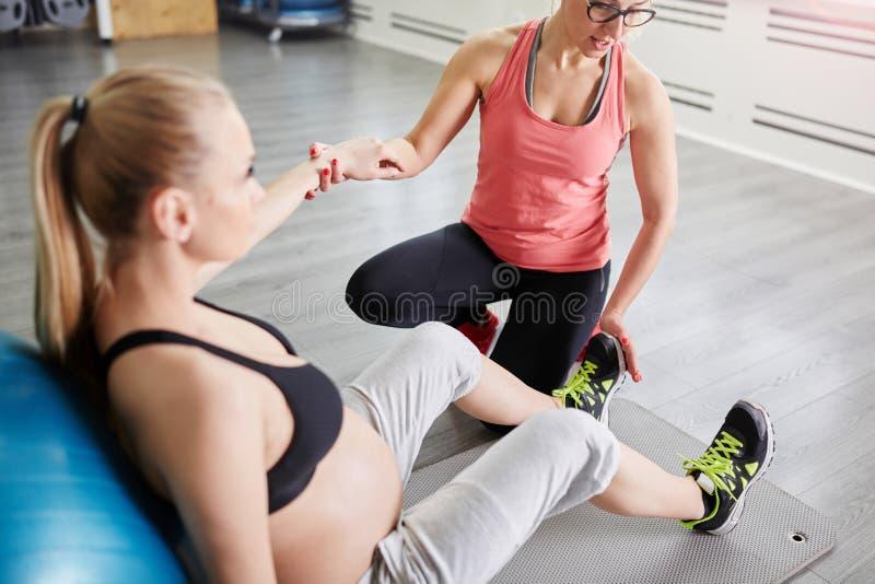 Zwangere vrouwenzitting op mat en persoonlijke trainer die haar h houden royalty-vrije stock foto's