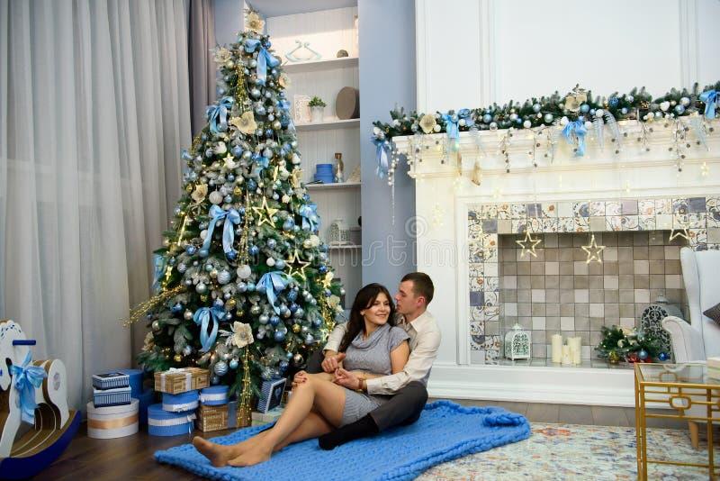 Zwangerschap, de wintervakantie en mensenconcept - gelukkige zwangere vrouw met echtgenoot thuis bij Kerstmis stock fotografie