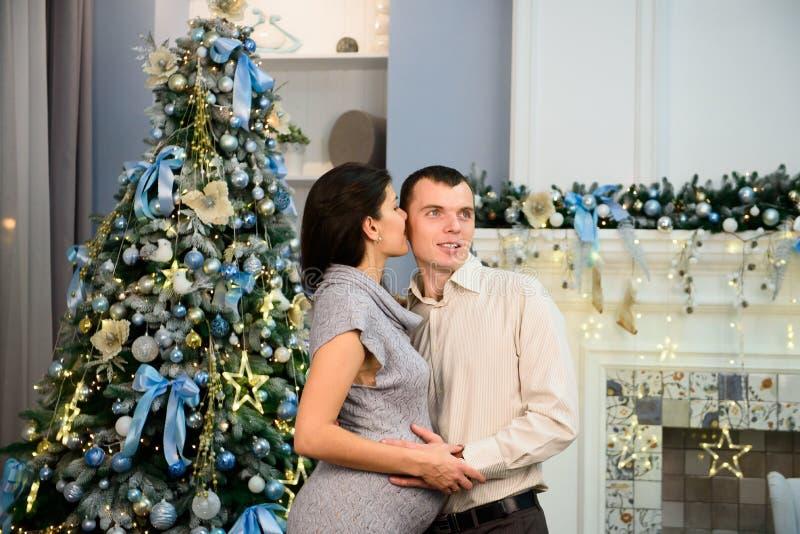 Zwangerschap, de wintervakantie en mensenconcept - gelukkige zwangere vrouw met echtgenoot thuis bij Kerstmis royalty-vrije stock foto's