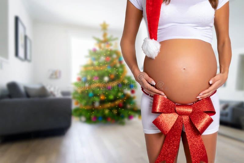Zwangerschap en Kerstmisconcept: zwangere vrouw met een rode boog op haar buik stock fotografie