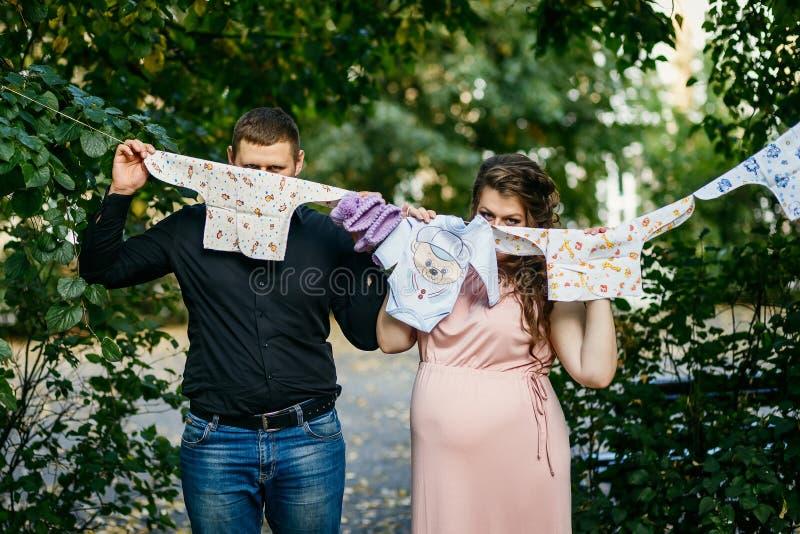 Zwangerschap, gehuwd jong paar met babykleren royalty-vrije stock afbeelding