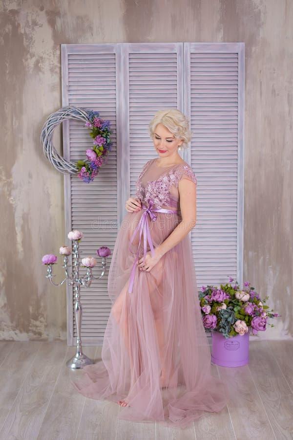 Zwangerschap, moederschap en gelukkig toekomstig moederconcept - de zwangere vrouw in luchtige violette kleding met boeket bloeit royalty-vrije stock fotografie