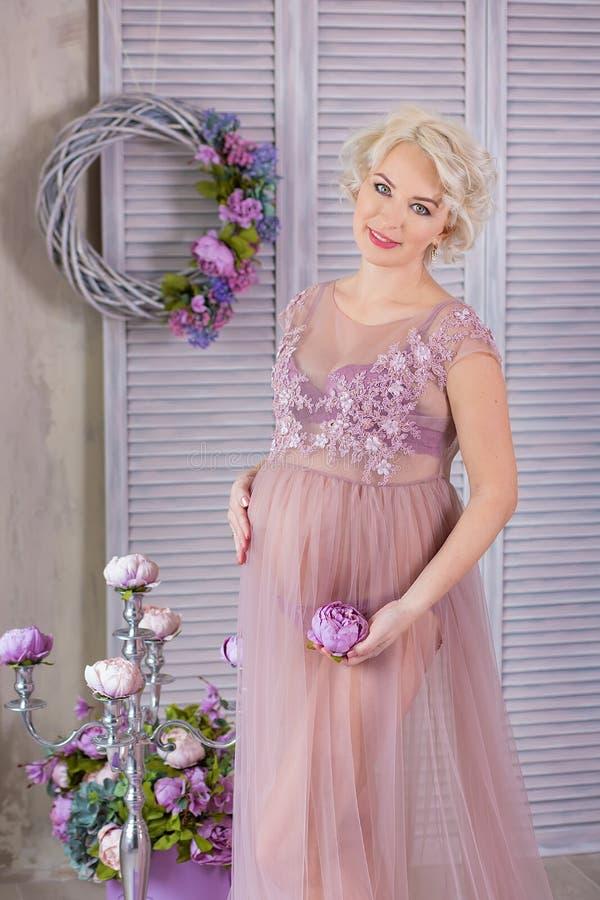 Zwangerschap, moederschap en gelukkig toekomstig moederconcept - de zwangere vrouw in luchtige violette kleding met boeket bloeit stock fotografie