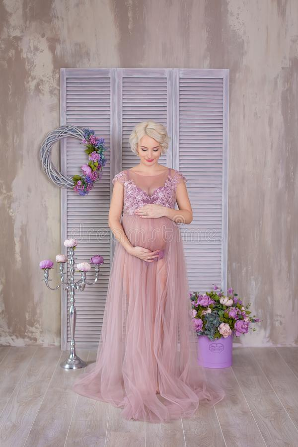 Zwangerschap, moederschap en gelukkig toekomstig moederconcept - de zwangere vrouw in luchtige violette kleding met boeket bloeit royalty-vrije stock foto