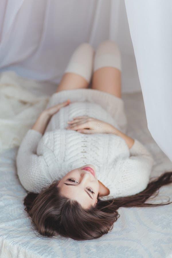 Zwangerschap, rust, en verwachtingsconcept - sluit omhoog van gelukkige glimlachende zwangere die vrouw liggend in bed met luifel royalty-vrije stock fotografie