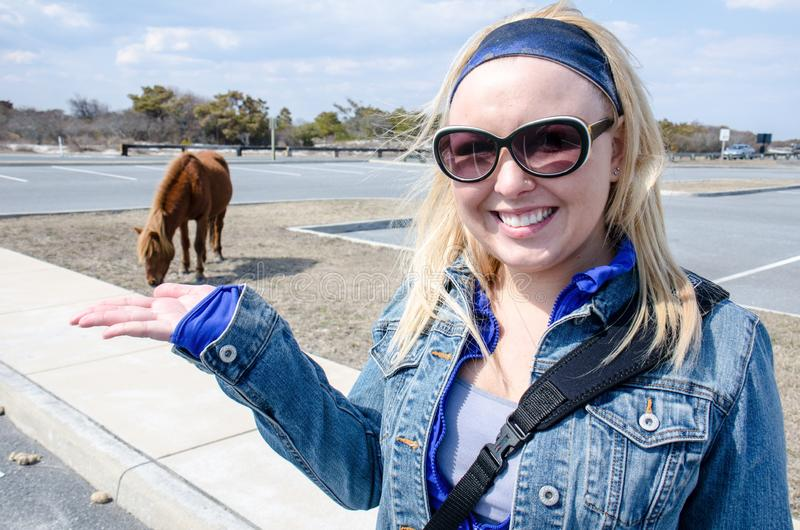Zwangsperspektive Blondine, die ein wildes Pferd außer Kontrolle essen lassen stockbilder