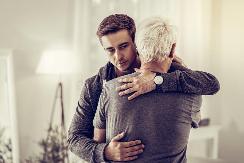Zwanzig-Jahr-alter dunkelhaariger netter Mann, der calmingly kranken traurigen alternden Opa streichelt stockbild