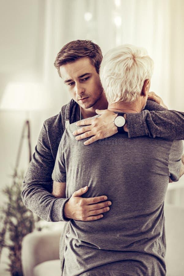 Zwanzig-Jahr-alter kurzhaariger netter Mann, der alten grau-haarigen Verwandten des kranken Umkippens umarmt stockbild