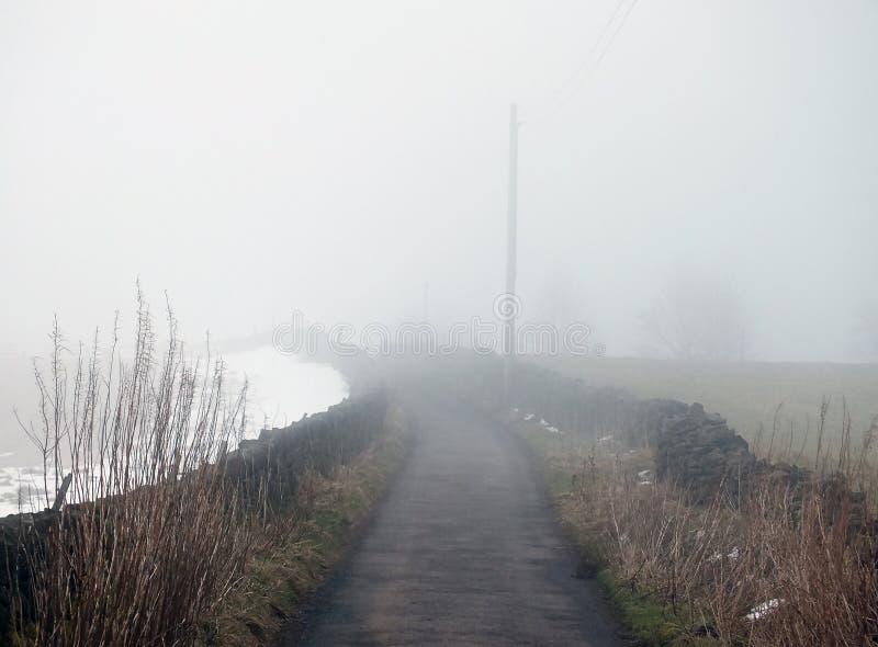 Zware dichte mist op een smalle verre landweg met sneeuw in het omringen van gebieden royalty-vrije stock afbeeldingen