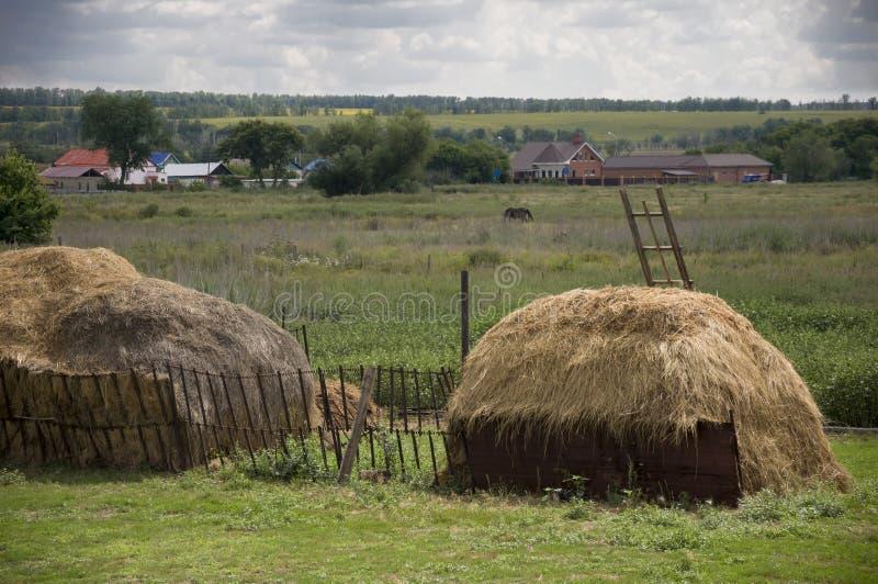 Zware grijze wolken in de koude de herfsthemel over dorp met plattelandshuisjes ver weg hayfield Er zijn rond vele stapels Travel stock afbeelding