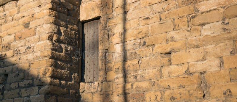 Zware houten deur met klinknagels aan de kant van een oude muur van het steenkasteel stock fotografie