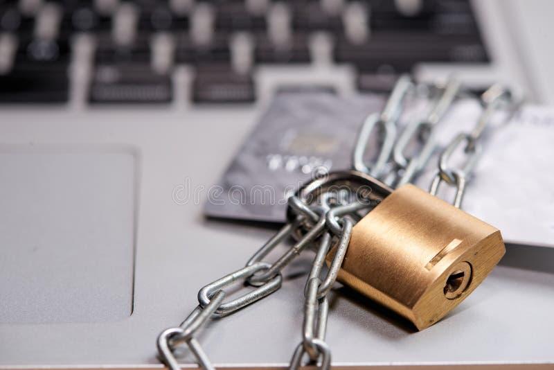 Zware ketting met een hangslot rond laptop en creditcard op Ta stock foto