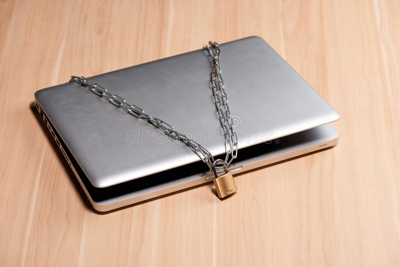 Zware ketting met een hangslot rond laptop op lijst stock afbeelding