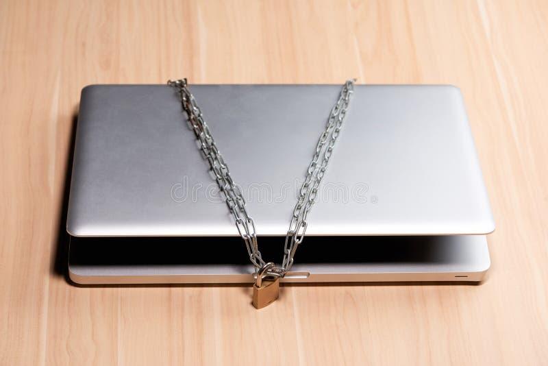 Zware ketting met een hangslot rond laptop op lijst royalty-vrije stock foto's