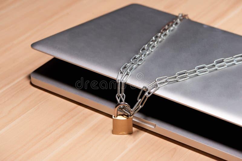 Zware ketting met een hangslot rond laptop op lijst stock afbeeldingen