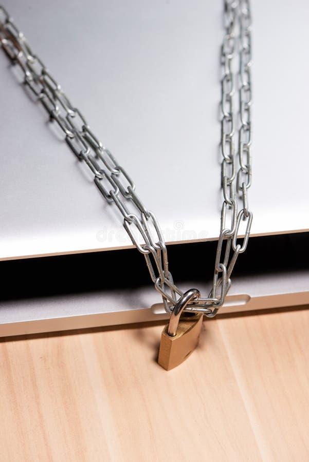 Zware ketting met een hangslot rond laptop op lijst royalty-vrije stock afbeeldingen