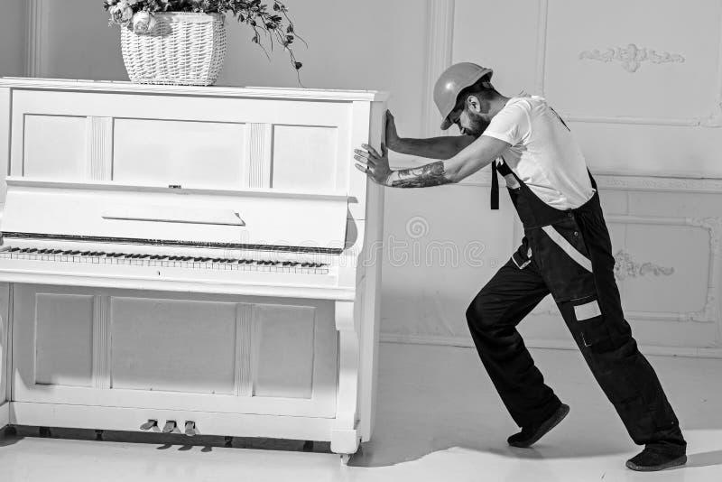 Zware ladingenconcept De lader beweegt pianoinstrument De koerier levert meubilair, beweging uit, verhuizing Mens met baard stock fotografie
