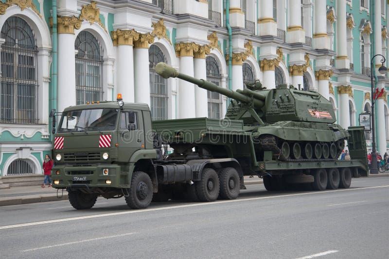 Zware militaire vrachtwagen kamaz-65225 met gemotoriseerde artillerie msta-S op de aanhangwagen Voorbereidingen voor de parade te stock foto