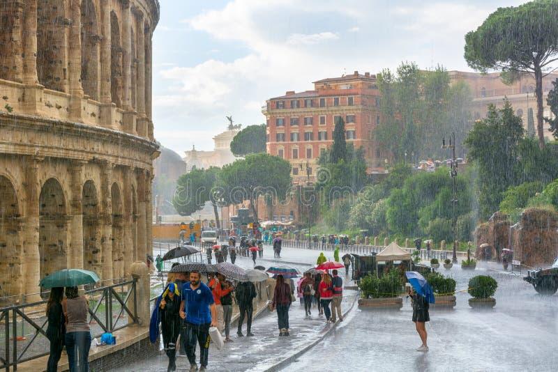 Zware regen, toeristen onder paraplu's, Colosseum royalty-vrije stock afbeelding