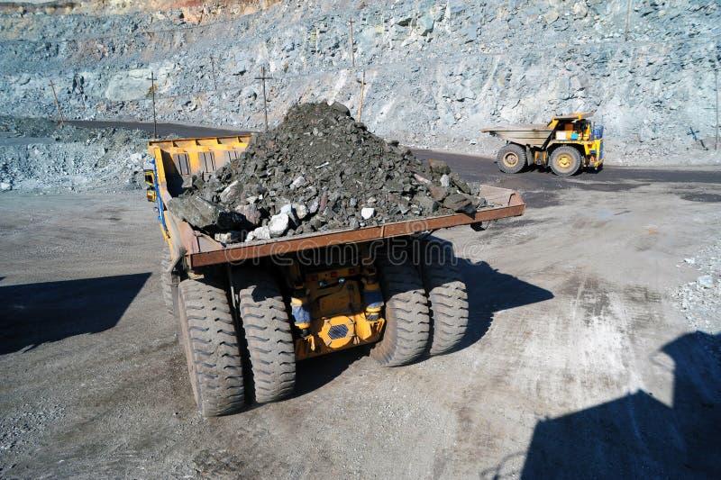Zware stortplaatsvrachtwagen die het ijzererts dragen stock afbeelding