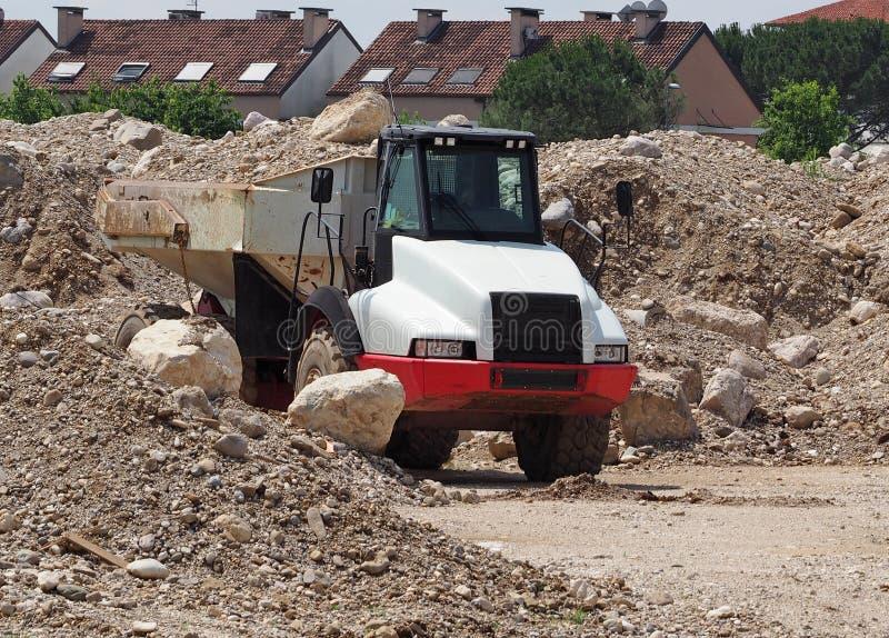Zware stortplaatsvrachtwagen onder duinen van grint van een nieuwe ontwikkelingsgebied stock foto's