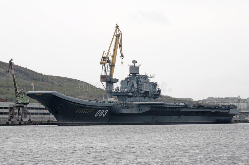 Zware vliegtuig-dragende kruiser` Admiraal Kuznetsov ` bij de muur van de haven van Moermansk stock foto