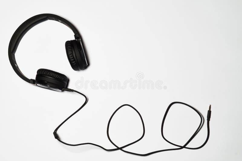 Zwart audiohoofdtelefoons en koord op witte achtergrond royalty-vrije stock fotografie