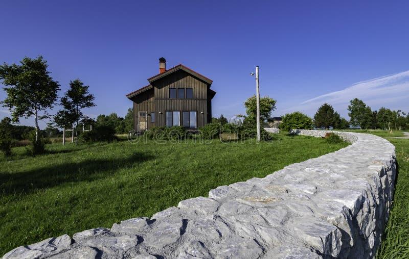 Zwart blokhuis met blauwe hemel en lange lage omheining royalty-vrije stock afbeeldingen
