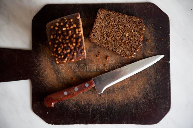 zwart brood met zonnebloemzaden op scherpe raad stock fotografie