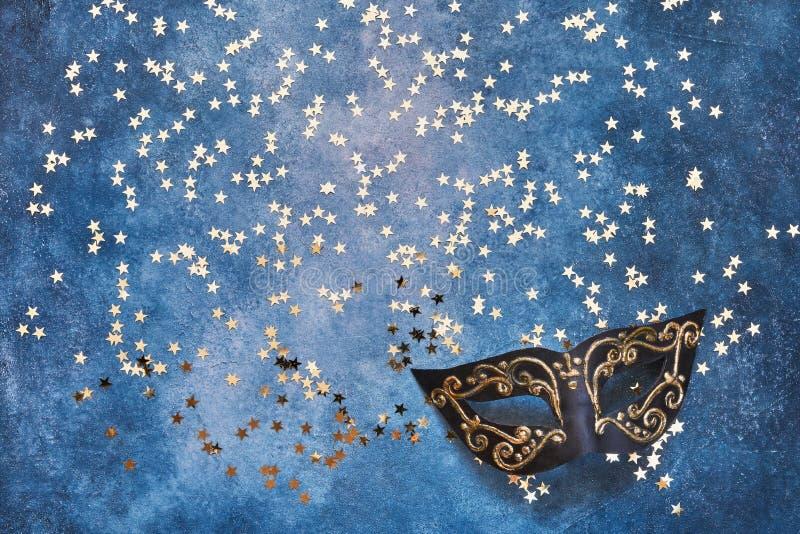 Zwart Carnaval-masker en gouden sterren op blauwe achtergrond Hoogste mening, exemplaarruimte stock foto's