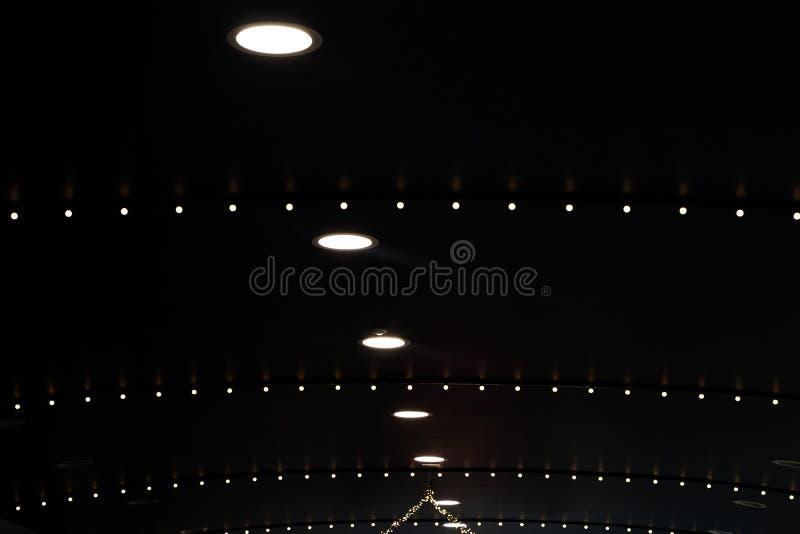 Zwart dak met witte cirkel ingebedde lichten en lijnen van kleinere lichten stock foto