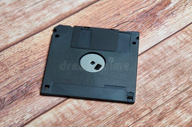 Zwart diskette oud formaat foto op houten achtergrond stock afbeelding