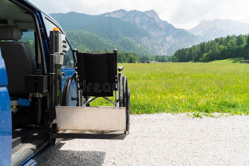 Zwart elektrisch lift gespecialiseerd voertuig voor gehandicapte mensen Lege rolstoel op een helling met aard en royalty-vrije stock afbeeldingen
