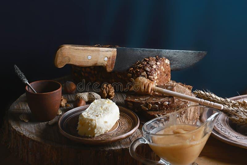 Zwart gesneden brood op de raad, het uitstekende mes, de boter en de honing, het lijnzaad, dan snijdend brood op de lijst en een  royalty-vrije stock foto's