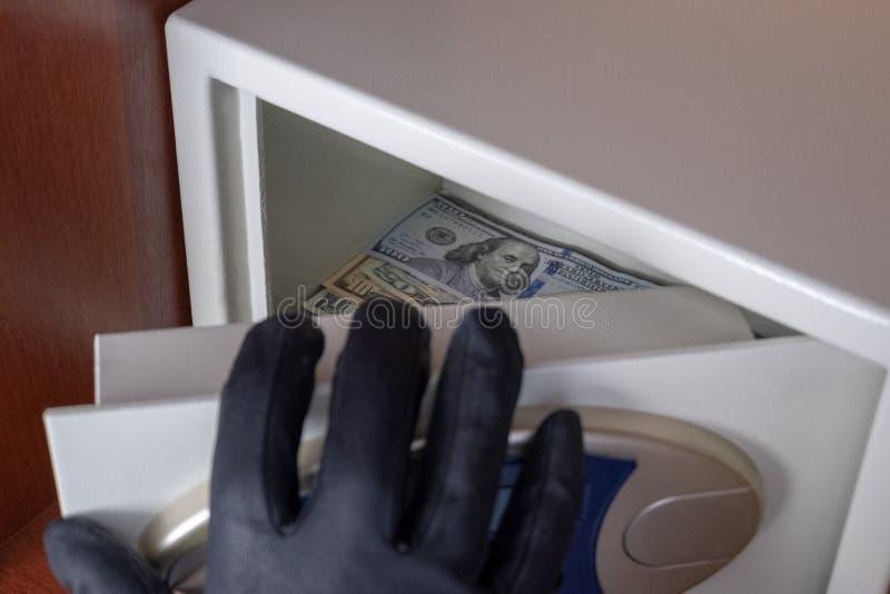 Zwart-gloved rechts opent de veilige deur van de stortingsdoos Diefstal van dollars van de brandkast Concept bescherming en veili stock fotografie