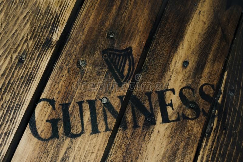 Zwart Guiness-bierembleem op plattelander doorstaan hout stock foto