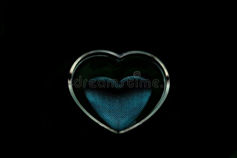 zwart hart op zwarte achtergrond stock afbeeldingen
