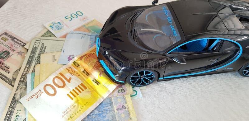 Zwart het metaalstuk speelgoed die van Bugatti Chiron zich met voorwielen op papiergeld van diverse landen bevinden stock foto