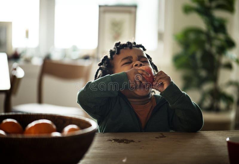 Zwart jong geitje die fruit eten stock foto
