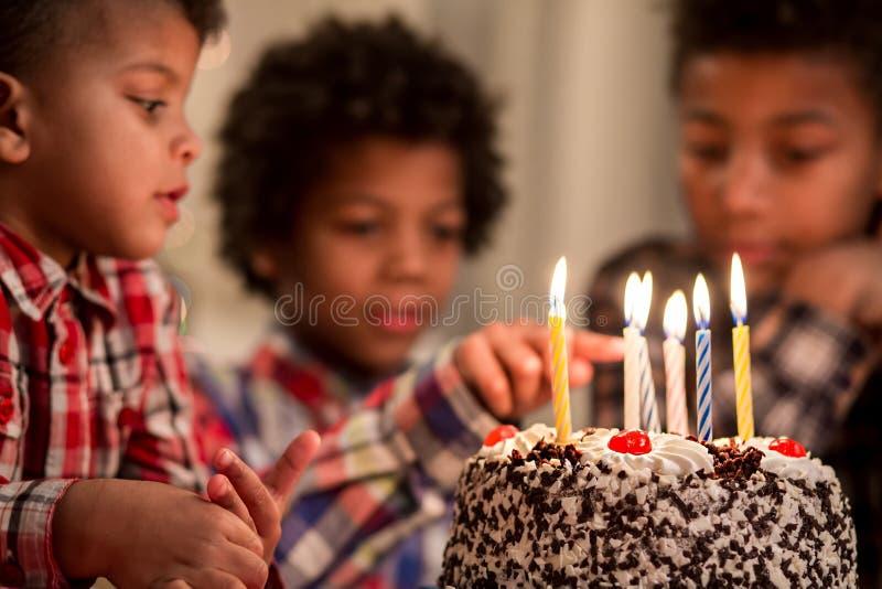 Zwart jong geitje wat betreft de kaars van de cake royalty-vrije stock fotografie
