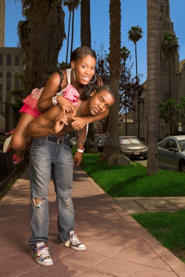 Zwart jong stedelijk paar dat pret in straat maakt stock afbeelding