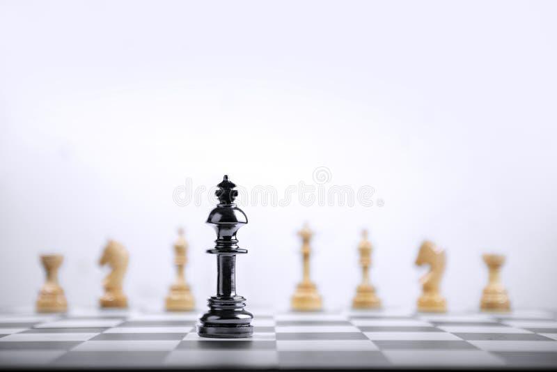 Zwart koningsschaakstuk die zich voor gehele groep houten schaakstukken bevinden stock foto's