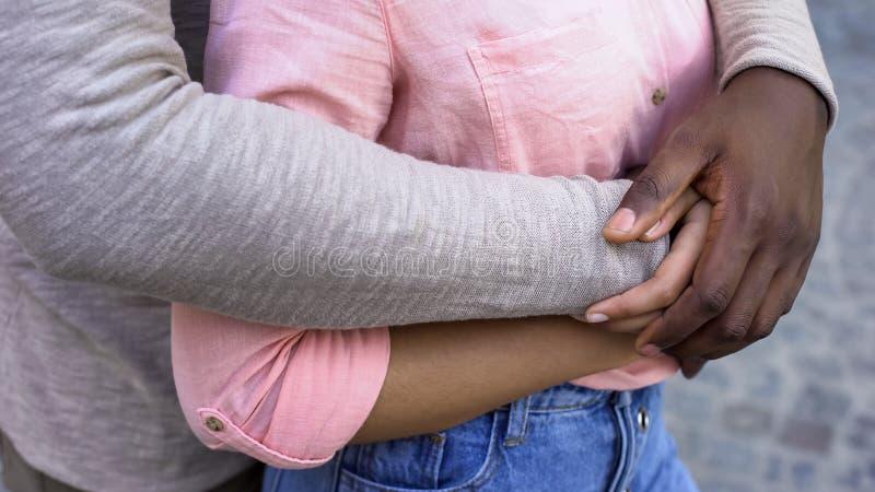 Zwart mannelijk koesterend meisje, romantische datum in stad, die veilig in relaties voelen stock afbeelding
