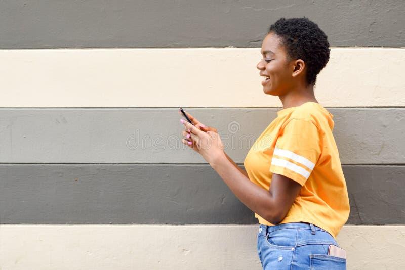 Zwart meisje die en haar smartphone in openlucht glimlachen met behulp van stock foto's