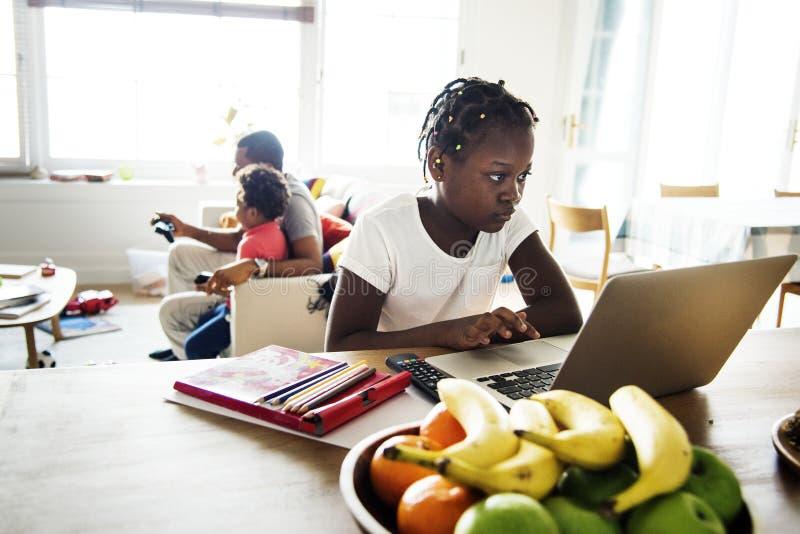 Zwart meisje die laptop thuis met behulp van stock foto's