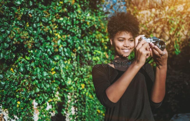 Zwart meisje die uitstekende filmnok in de tuin met behulp van stock foto's