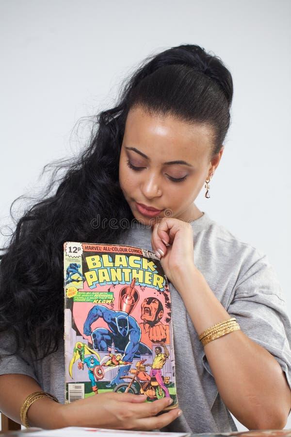 Zwart meisje die zwarte panter grappig houden stock afbeelding